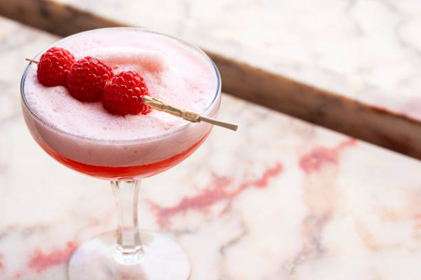 Pink Clover Club Cocktail with Egg White Foam and Raspberry Garnish stock photo
