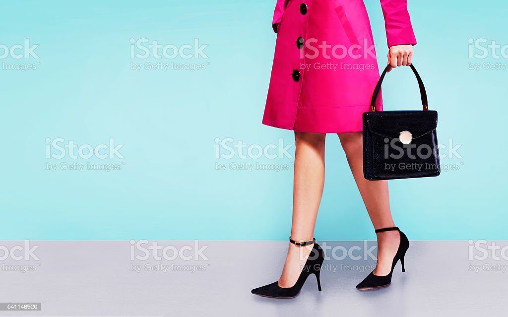 Pink coat woman with black leather handbag with heels shoes. stock photo