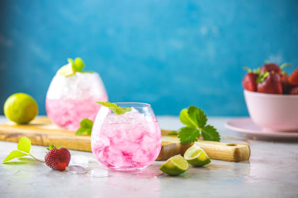 Pink cocktail with lime, crushed ice, strawberries and mint on the light background, selective focus image, copy spice for you text, summer vacation and party concept. stock photo