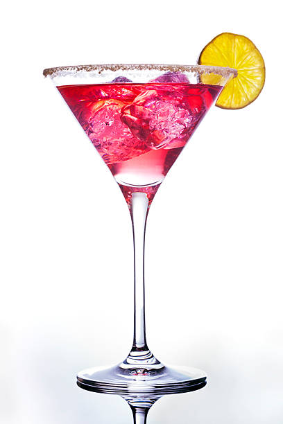 Pink colored cocktail adorned with an orange slice Manhattan cocktail with lime and ice cubes on reflective surface. martini glass stock pictures, royalty-free photos & images