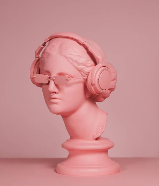 déesse grecque moderne de couleur rose avec des écouteurs - fond couleur uni photos et images de collection