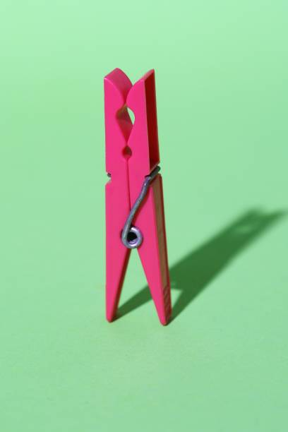 pink colored plastic clothespin on green background. Minimal concept art. Shadows. Color clothes-peg isolated. stock photo