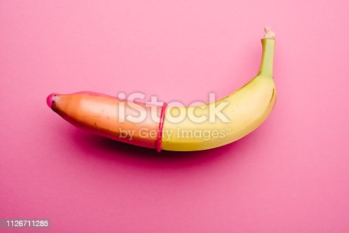 Pink condom on fresh yellow banana in front of pink background