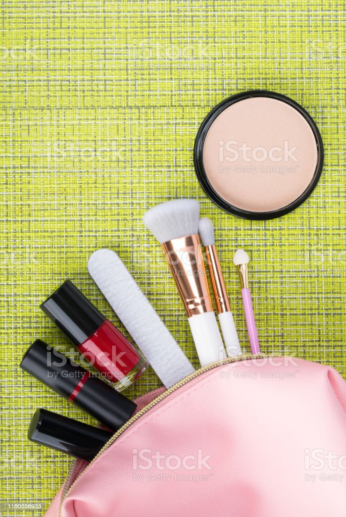 pink cosmetic bag with neatly laid out makeup items on a green...