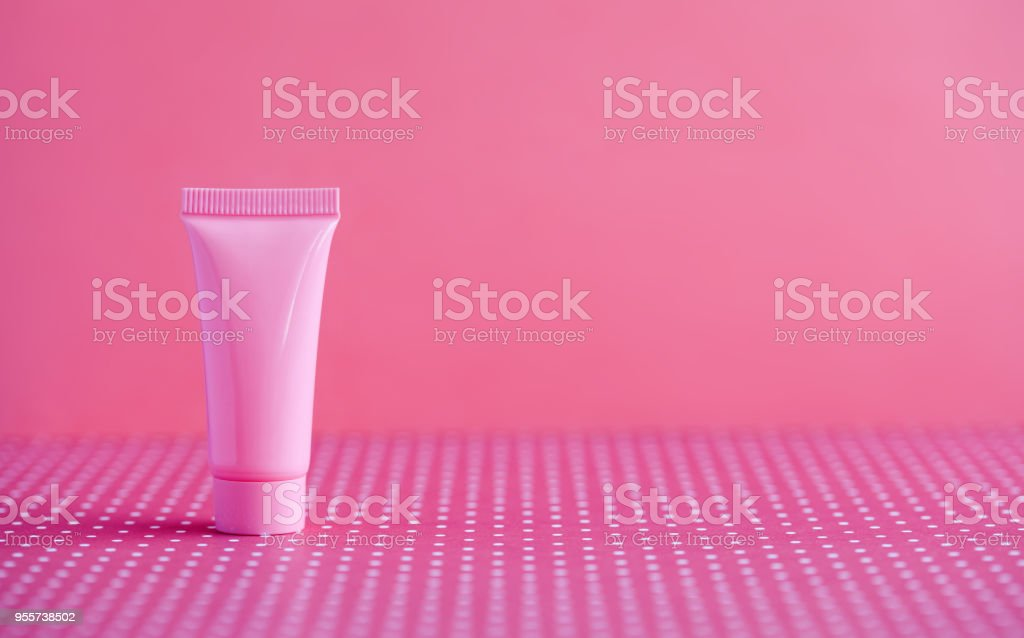 Pink cosmetic tube on pink polka dot background. Blank plastic...