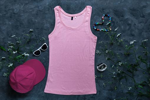 Pink cotton tank top mockup on dark background Blank plain t-shirt template for creative design Female summer sunglasses
