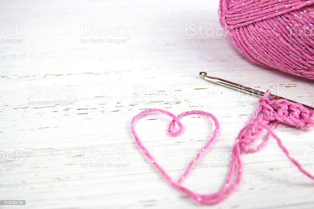 pink crochet background with yarn heart stock photo