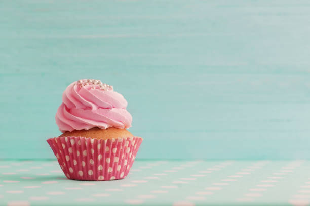 pink cupcake on blue wooden background - cupcake foto e immagini stock