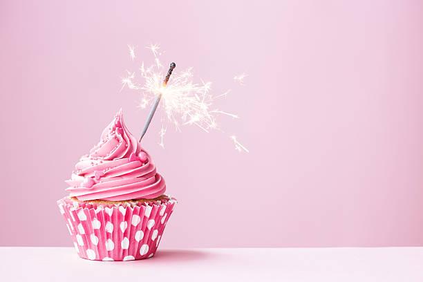 rosa cupcake con candela magica - cupcake foto e immagini stock