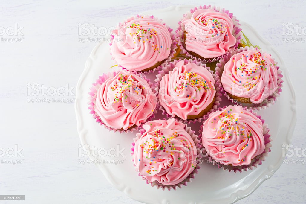 Pink cupcakes  on cake stand top view stock photo