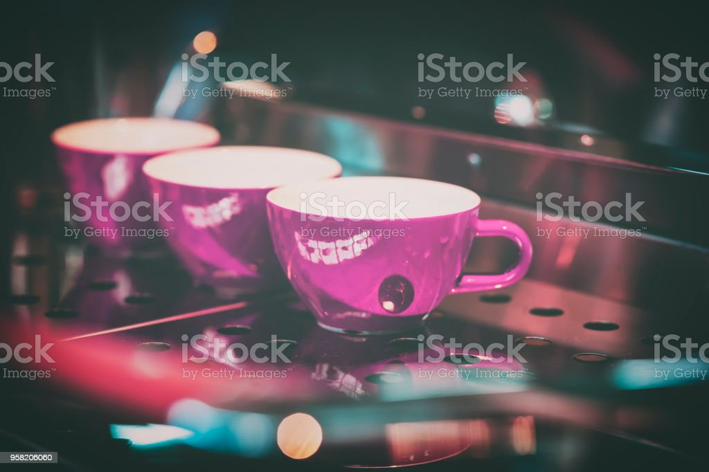 Pink cups on the stand of the coffee machine, bar. Vintage dark tone,...