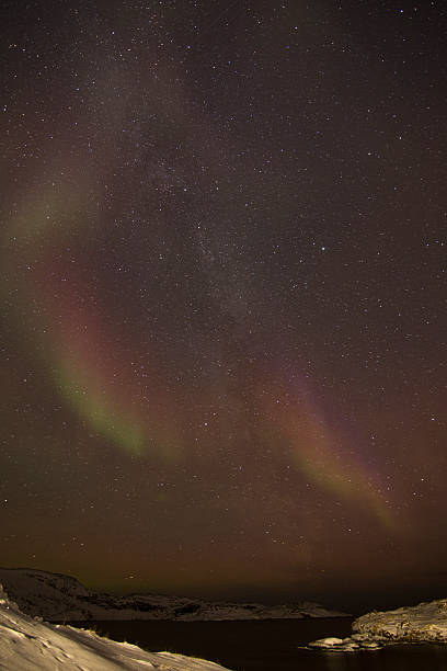 Pink curved Aurora Borealis over bay stock photo
