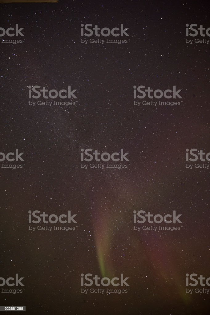 Pink curved Aurora Borealis with milkyway stock photo
