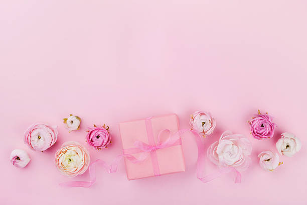 pink desk with flowers and gift for holiday. flat lay. - hochzeitsbox stock-fotos und bilder
