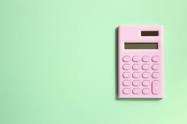 rosa digitalrechner auf grünem hintergrund - pastellstifte stock-fotos und bilder