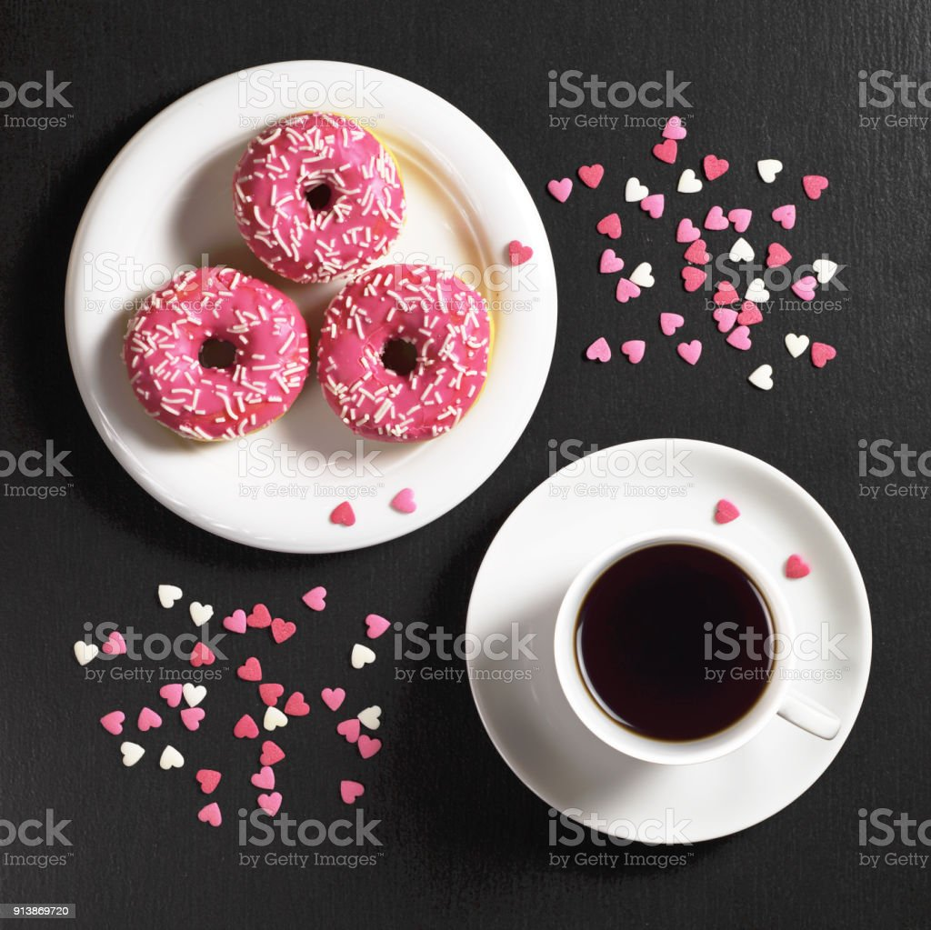 Pink donuts with sprinkles in plate and cup of coffee on black stone...