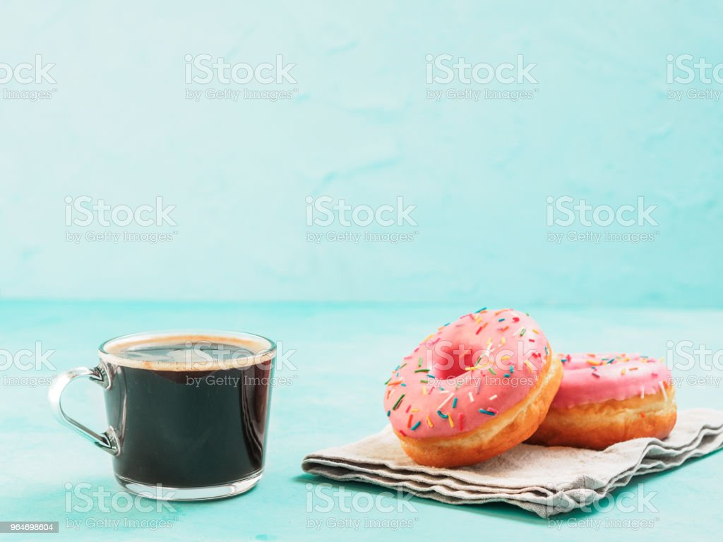 pink donuts on blue background , copy space royalty-free stock photo