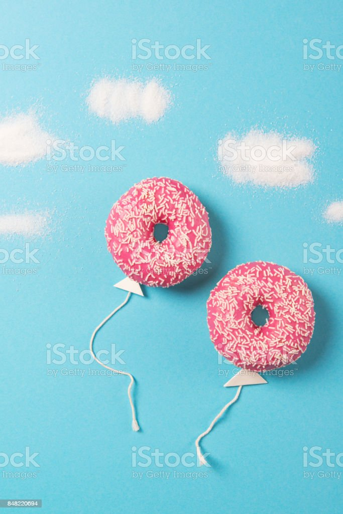 Pink donuts on blue background, creative food minimalism, donut in a shape of balloon in the sky with clouds made of sugar, top view stock photo