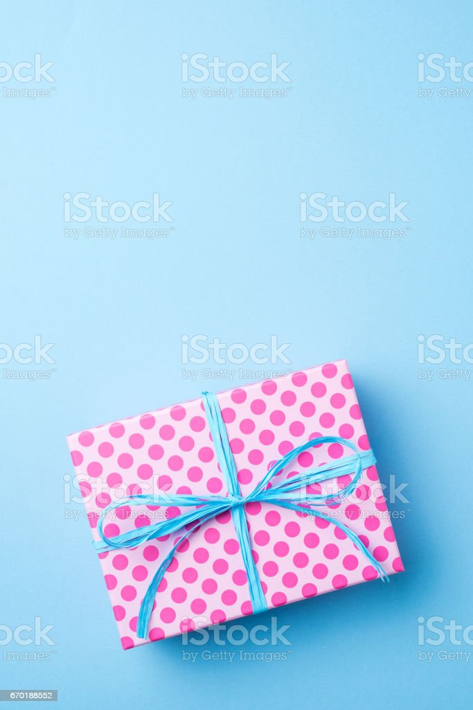 Pink dotted gift box on blue background stock photo