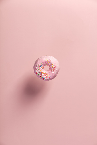 istock Pink doughnut with sprinkles falling or flying in motion 930716278