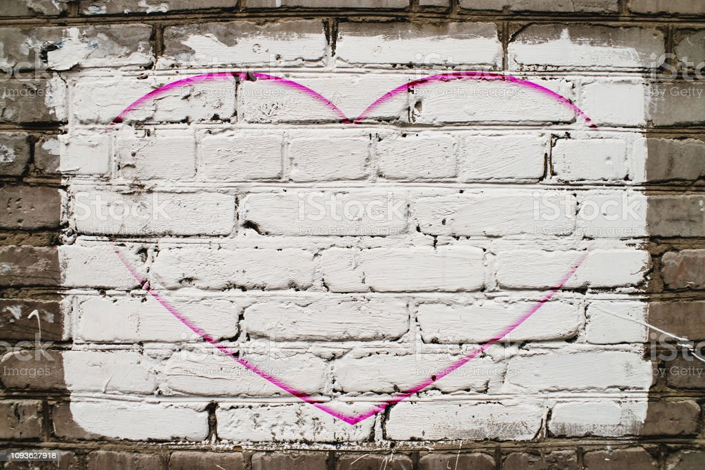 Pink drawn heart on brick wall with white paint close-up. Mock up....