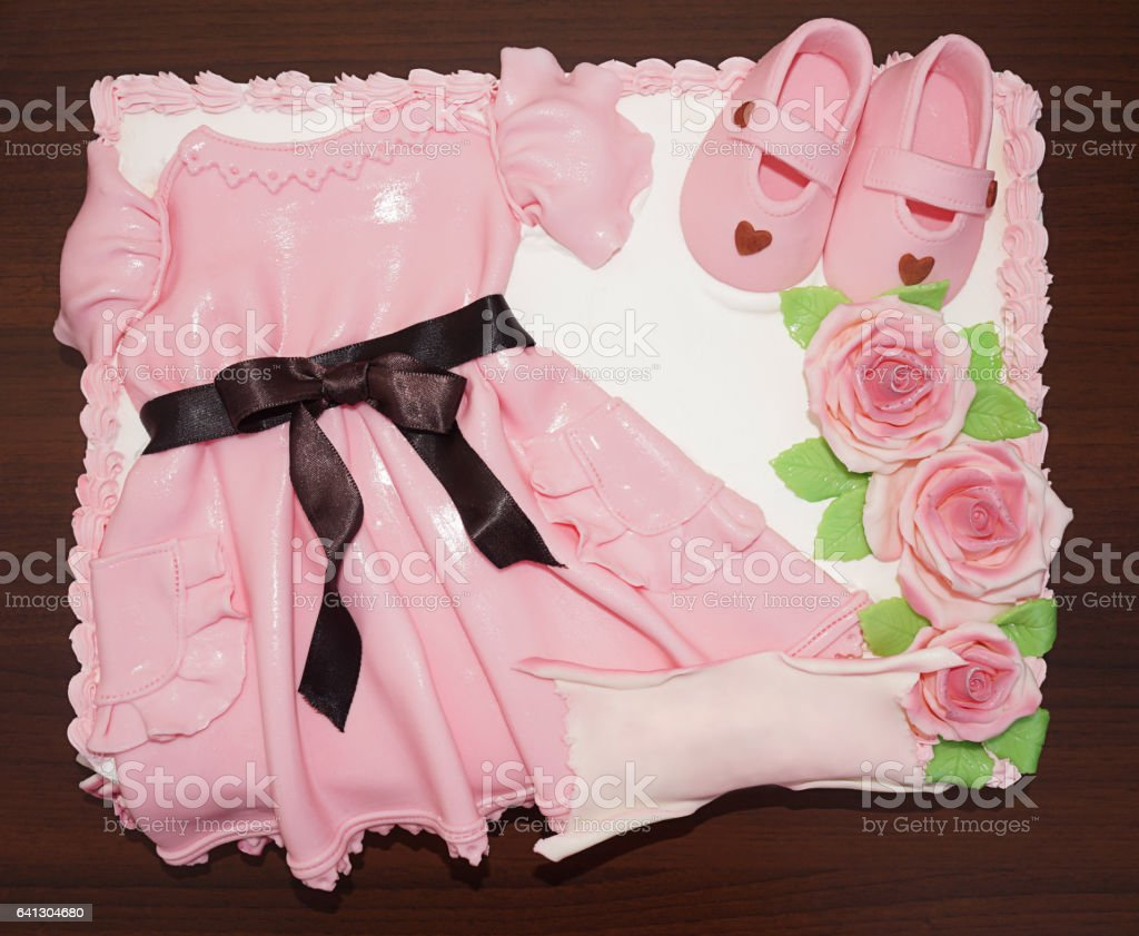 Pink dress cake with shoes and flowers for christening baptism - Stock  image . b34eee33f87e