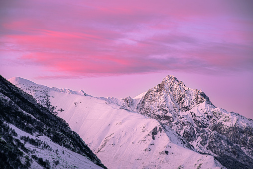pink early morning glow light on snow covered mountains in arctic norway, super wide panoramic scene