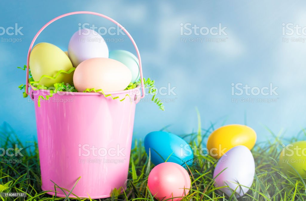 A Pink Easter Basket Filled with Diecorated Eggs on a Clear Blue Sky Spring Day royalty-free stock photo