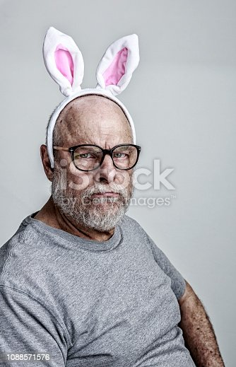An authentic, humorous, real person, real life senior adult man chemotherapy patient with a mock-serious, mock-frowning, semi-smirking facial expression is wearing a playful pink Easter Bunny ears hair clip on his balding head above his nerdy black-rimmed glasses. Deliberately bizarre and maybe even a little creepy, but he's making the best of a serious situation - the ongoing fight to survive cancer.  The week before this photo, he finished a three month bi-weekly chemotherapy regimen that had followed an emergency hospital surgery to remove a malignant intestinal cancer tumor. Along with constant general weariness, his main chemo drug side effects are considerably thinner beard and mustache facial hair; and many new skin blemishes and liver spots on his head and neck. Oh, and those odd pink Easter bunny ears!