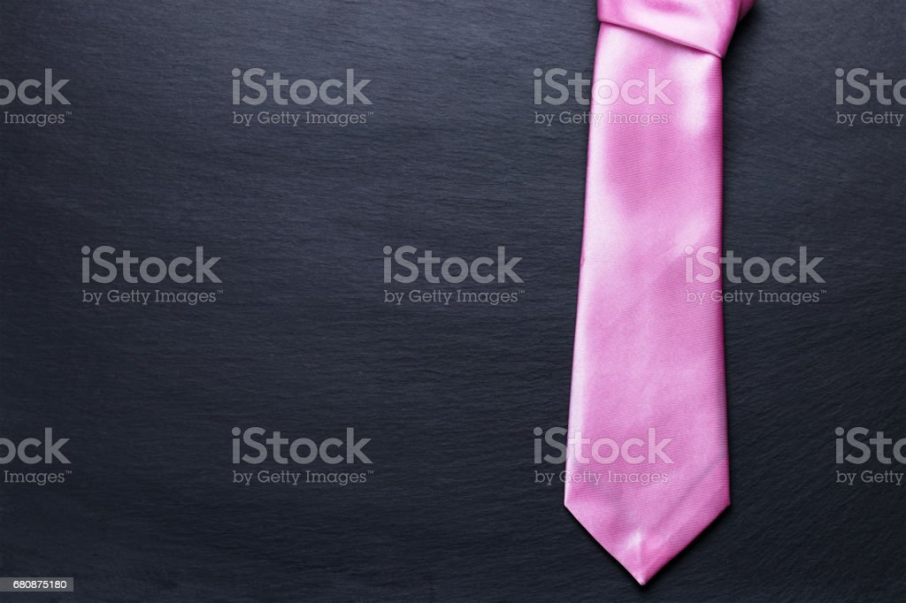 Pink elegant tie on black textured background. royalty-free stock photo