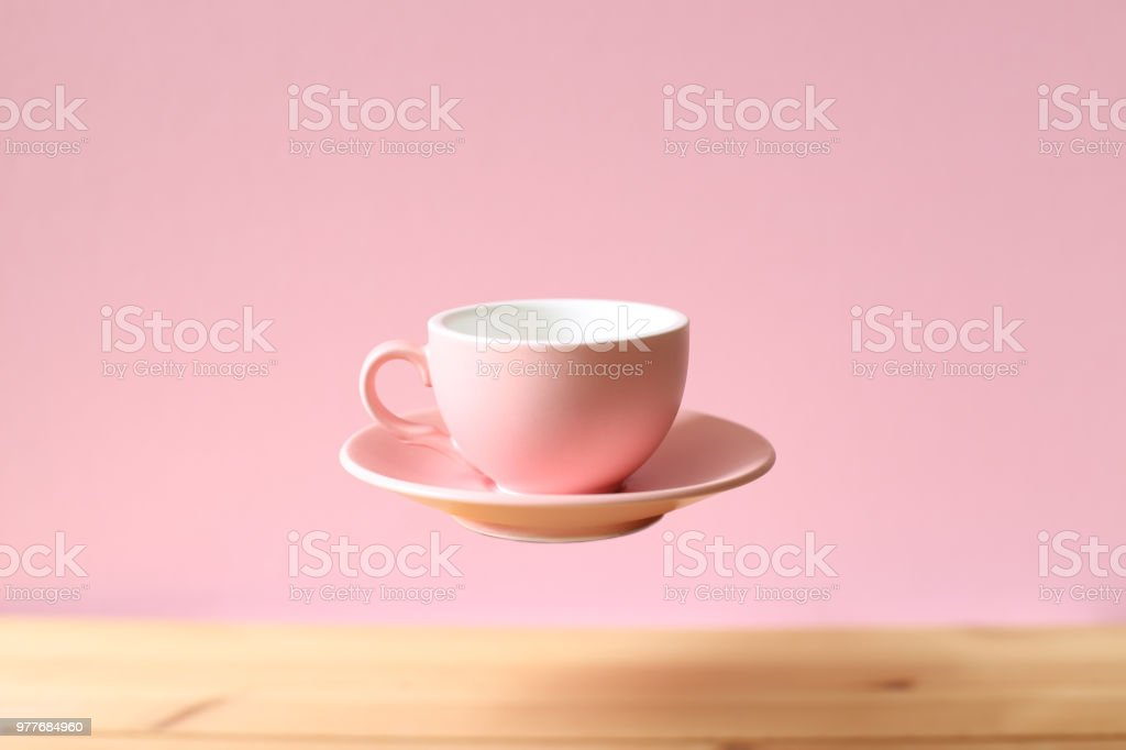 Pink empty coffee cup floating on wooden table