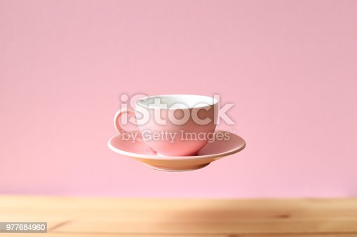 istock Pink empty coffee cup floating on wooden table 977684960