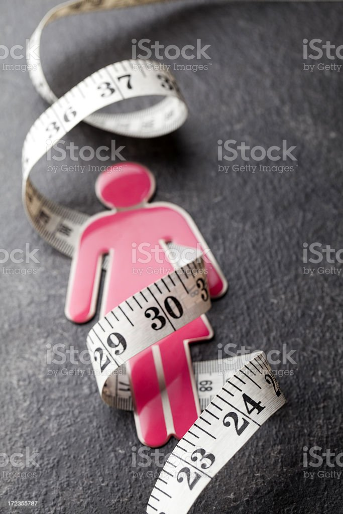 Pink female figure with tape measure royalty-free stock photo