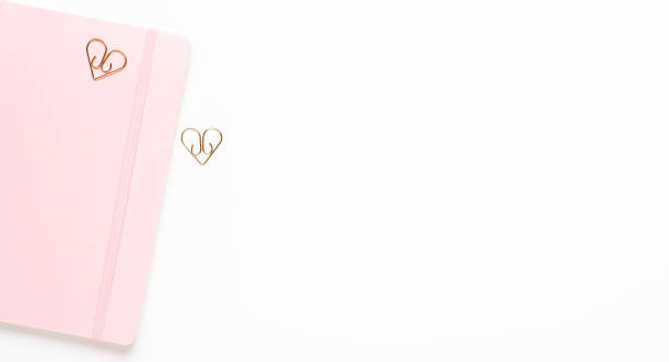 Pink female notebook with golden clips of stars on a white background. Copy space, top view, flat lay. stock photo