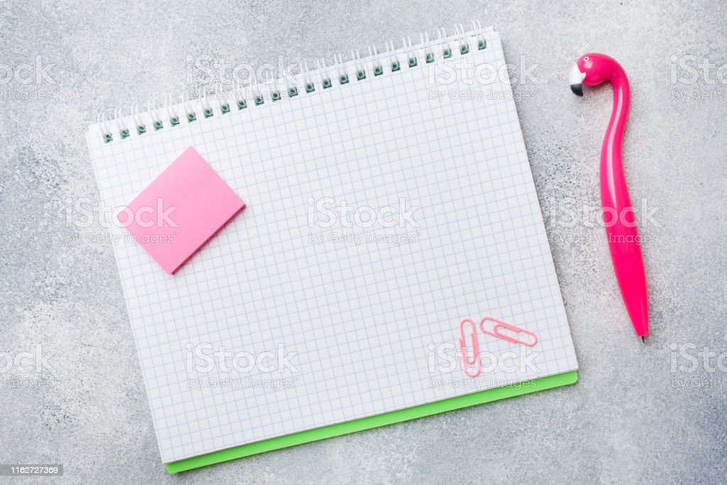 Pink Flamingo pen and writing pad on grey background. Copy space flat...