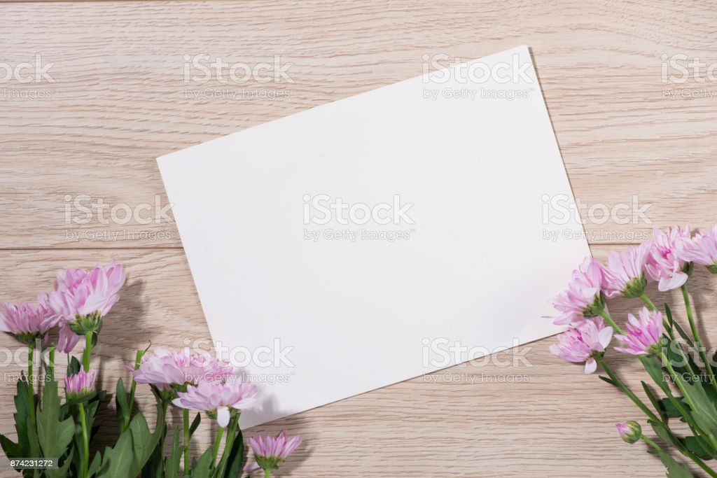 Pink flowers and empty paper for your text on wooden background stock photo