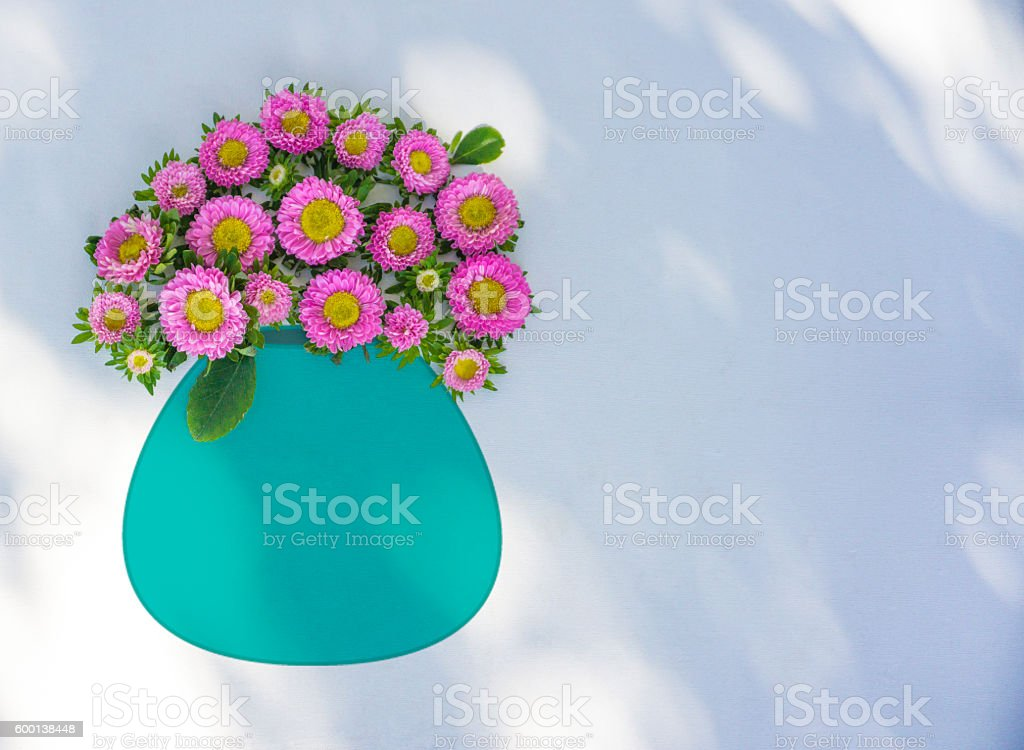 Pink flowers in a turquoise vase stock photo
