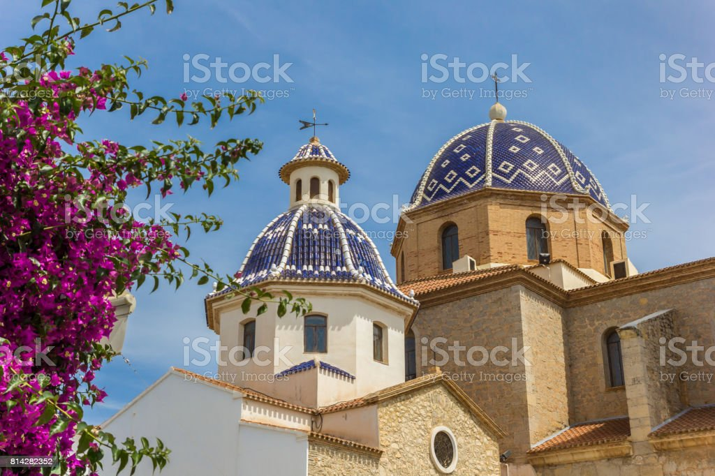 Flores de color rosa frente a las cúpulas azules de la iglesia de Altea, España - foto de stock