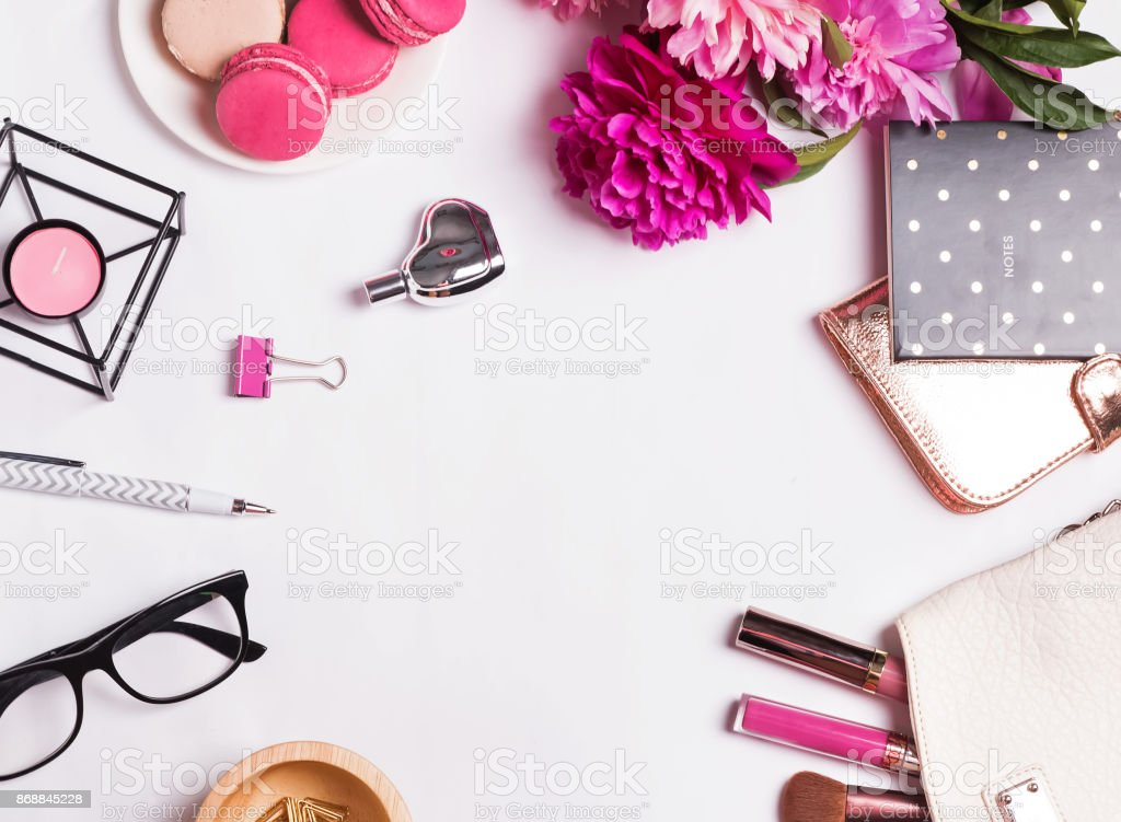 Pink flowers, macarons, feminine accessories on the white