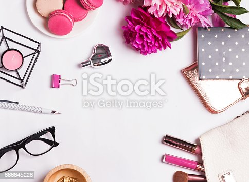 istock Pink flowers, macarons, feminine accessories on the white 868845228