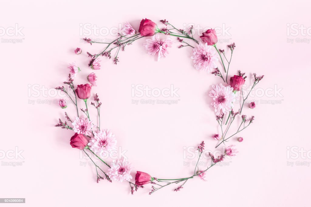 Flowers composition. Wreath made of pink flowers on pink background....