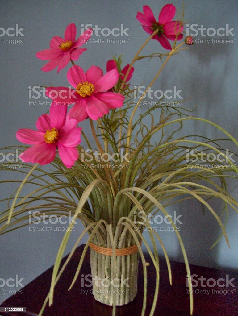 Pink Flowers with Long Green Leaves on Dark Wooden Table stock photo