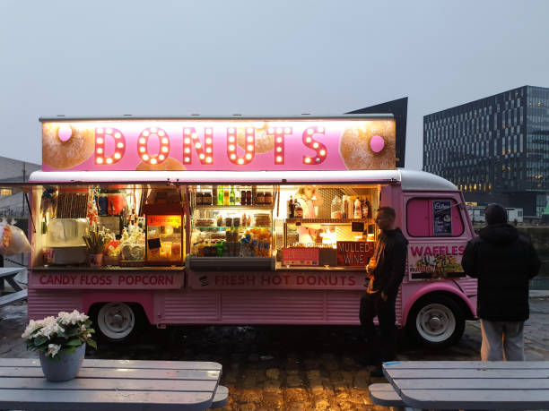 Pink food truck offering donuts and waffles at the Albert Dock waterfront in Liverpool,Great Britain stock photo