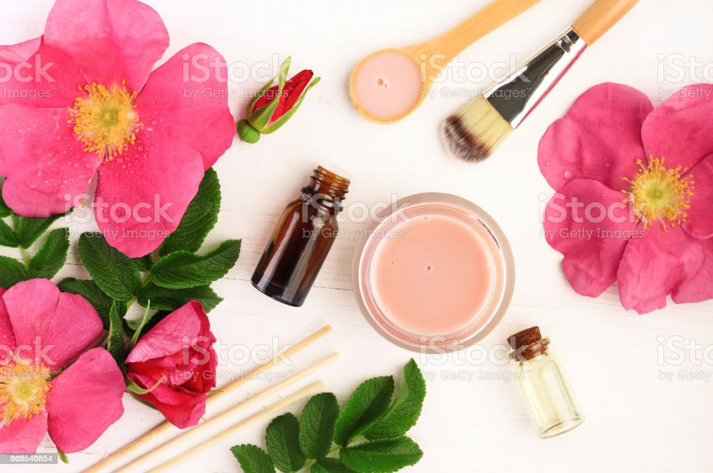Pink fresh wild rose flowers and leaves, bottles and jars, top view. stock photo