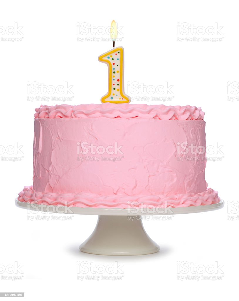 Pink frosted birthday cake with number 1 candle lit on top royalty-free stock photo