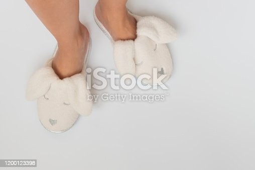 Pink fur slippers in shape of rabbit put on women legs standing on a white background.Top view. Copy space