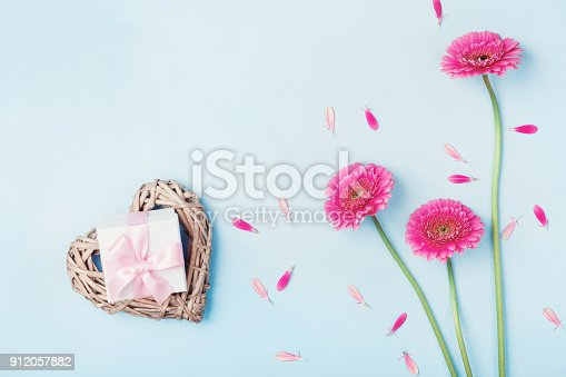 istock Pink gerbera flowers, heart and gift box on blue table top view. Greeting card for Birthday, Woman or Mothers Day. 912057882