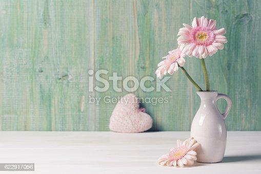 istock Pink Gerbera flowers in vase on green wooden background 622917056