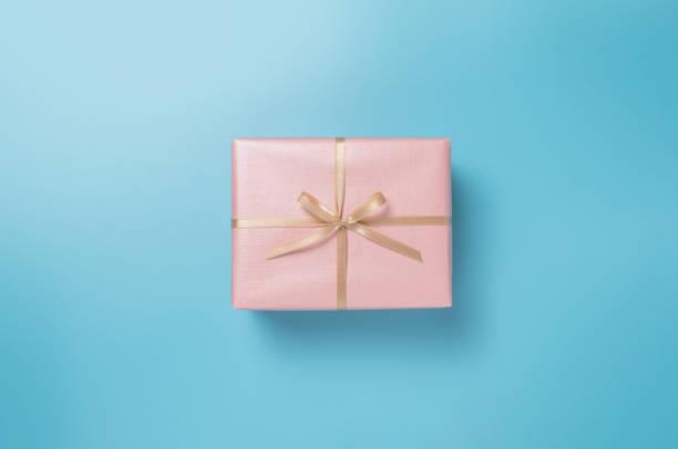 caja de regalo rosa con cinta de oro sobre fondo aislado azul - foto de stock
