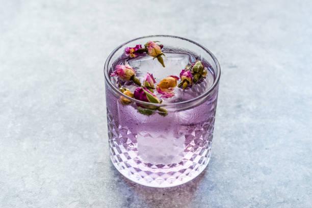 Cocktail tonic cor-de-rosa do gin com botões e gelo cor-de-rosa secados no copo de vidro - foto de acervo